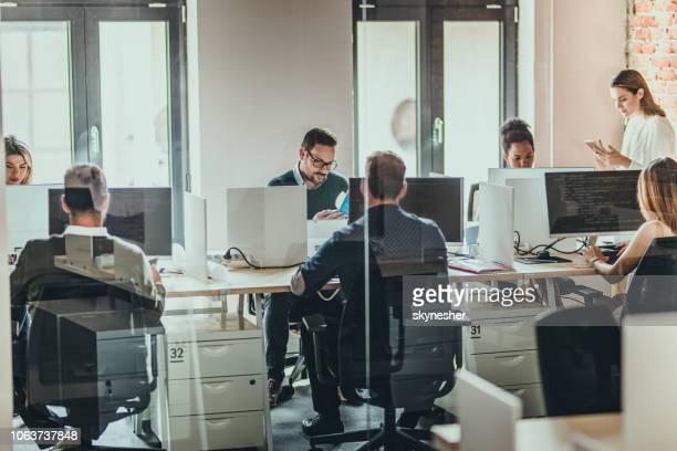 grote groep programmeurs werkt aan desktop-pc's in het kantoor. - kantoor stockfoto's en -beelden