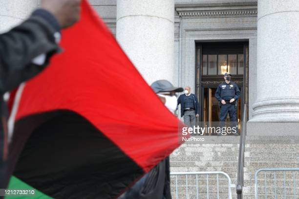 A large group of protesters bound together with yellow caution tape marched on New York's Police Headquarters decrying police brutality against...
