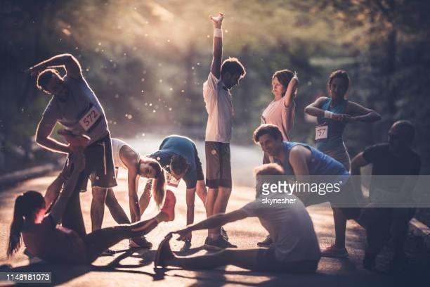 grande grupo de corredores que aquecem-se acima em uma estrada no por do sol antes da maratona. - equipe esportiva - fotografias e filmes do acervo