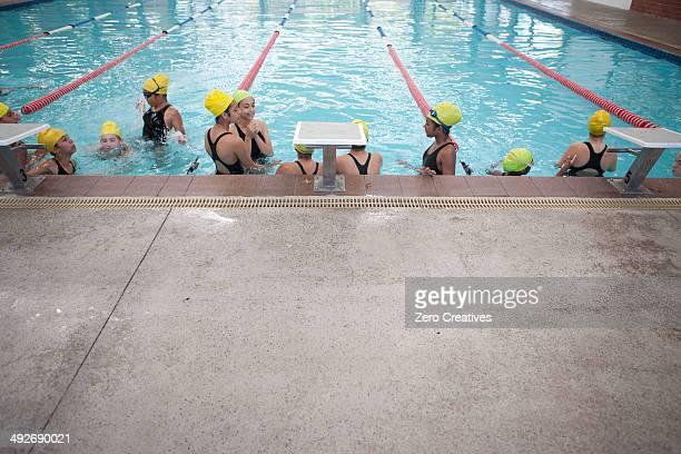 Large group of schoolgirls taking a break in swimming pool