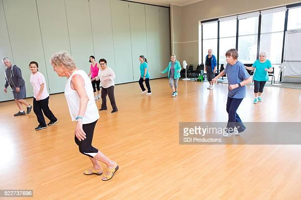 Large group of seniors take line dancing class