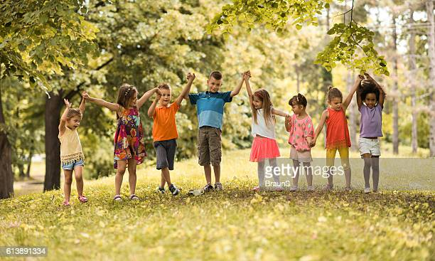 Large group of small children holding hands in nature.