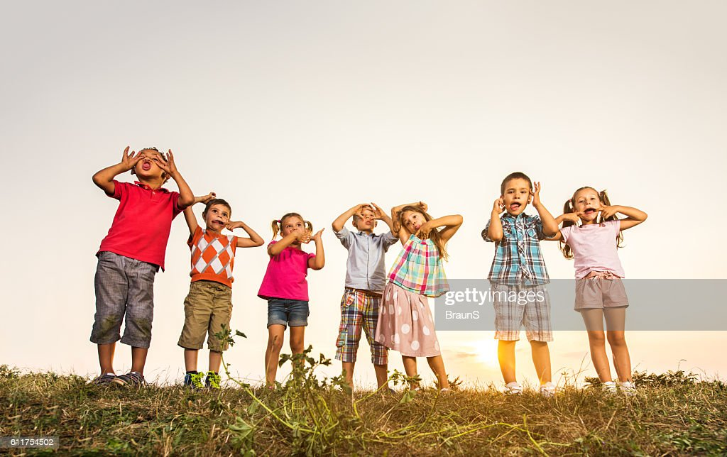 large group of small kids making faces at sunset stock photo - Pictures Of Small Kids