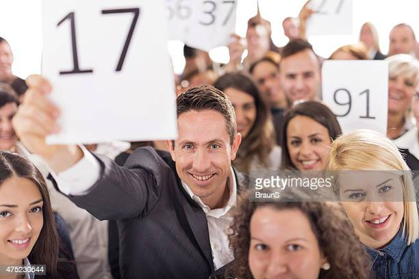 Large group of smiling business people at auction.