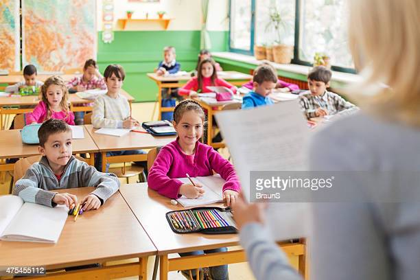 large group of smiling elementary students attending a class. - bijwonen stockfoto's en -beelden