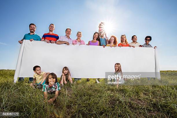 Large group of smiling people holding blank placard in nature.