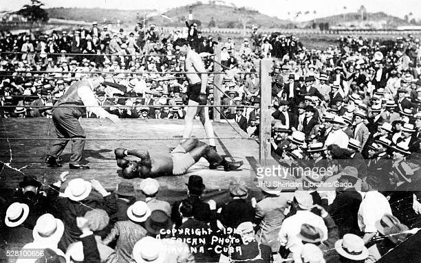 A large group of spectators stands around an outdoor boxing ring in which are Jack Johnson a referee and Jess Willard who has just knocked out...