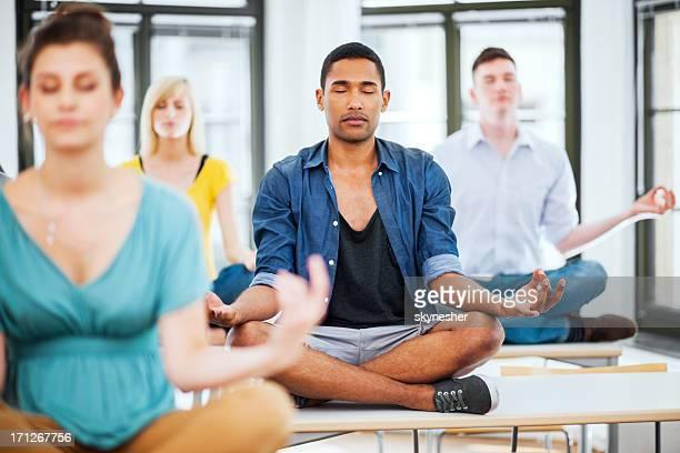 Gran grupo de estudiantes Meditando en el escritorio