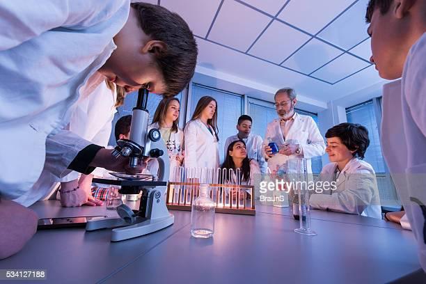Große eine Gruppe von Studenten auf eine Chemie Klasse mit Lehrer.