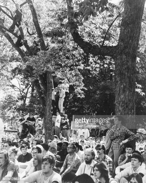 A large group of students wearing hippie attire gather on a quad some climbing trees in order to find their spot and listen to a speaker during an...