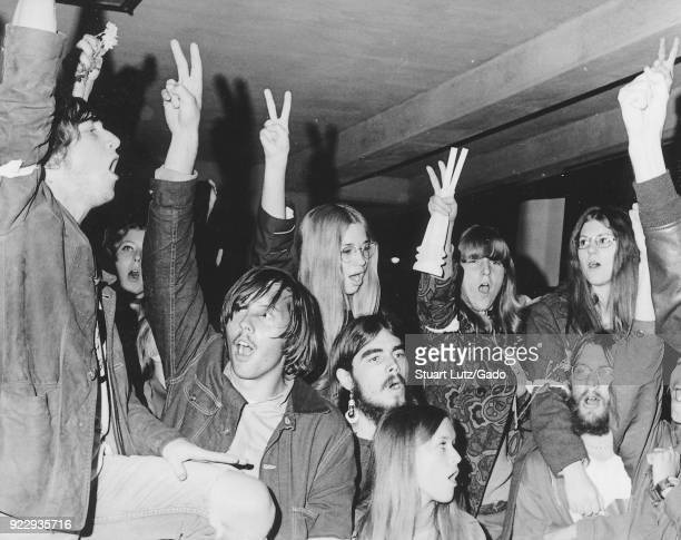 A large group of students wearing hippie attire including psychedelic patterned clothing antiwar armbands and long hair hold their fingers aloft in a...