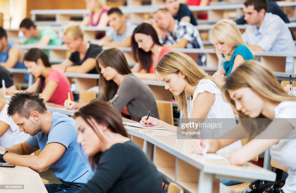 Large group of students writing in notebooks. : Stock Photo