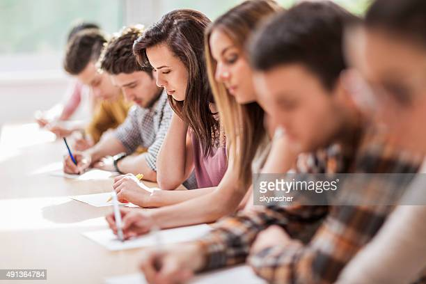 Large group of students writing in the classroom.