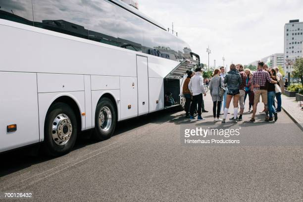 Large group of Tourist waiting to get on Bus