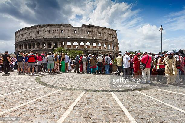 CONTENT] Large group of tourists admiring the Colosseum in Rome in summertime