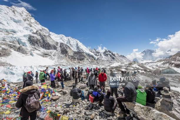 large group of tourists standing at Mount Everest base camp in sunshine