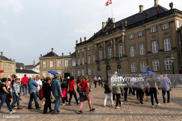 Large group of tourists walk towards Crown prince Frederiks and Crown Princess Marys residence, Frederik VIIIs palace at Amalienborg on August 28,...
