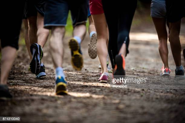 large group of unrecognizable athletes running a marathon in nature. - running stock pictures, royalty-free photos & images