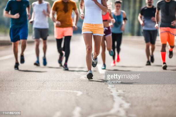 large group of unrecognizable marathon runners having a race on the road. - half_marathon stock pictures, royalty-free photos & images