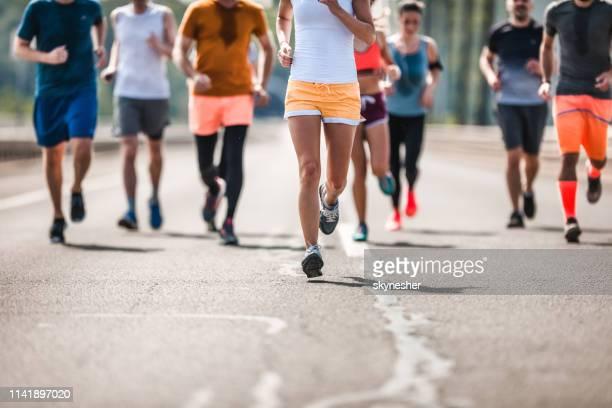 道路上のレースを持つ認識できないマラソンランナーの大規模なグループ。 - ハーフマラソン ストックフォトと画像