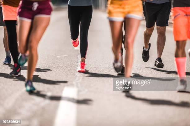 large group of unrecognizable marathon runners having a race on the road. - track event stock pictures, royalty-free photos & images