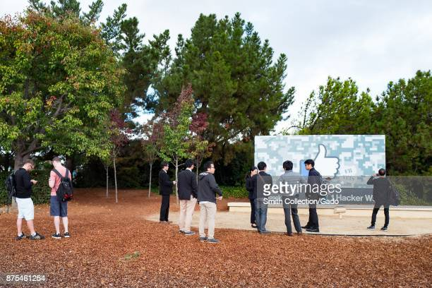 A large group of visitors stands with the main sign at the entrance of the headquarters of Facebook in Silicon Valley Menlo Park California November...