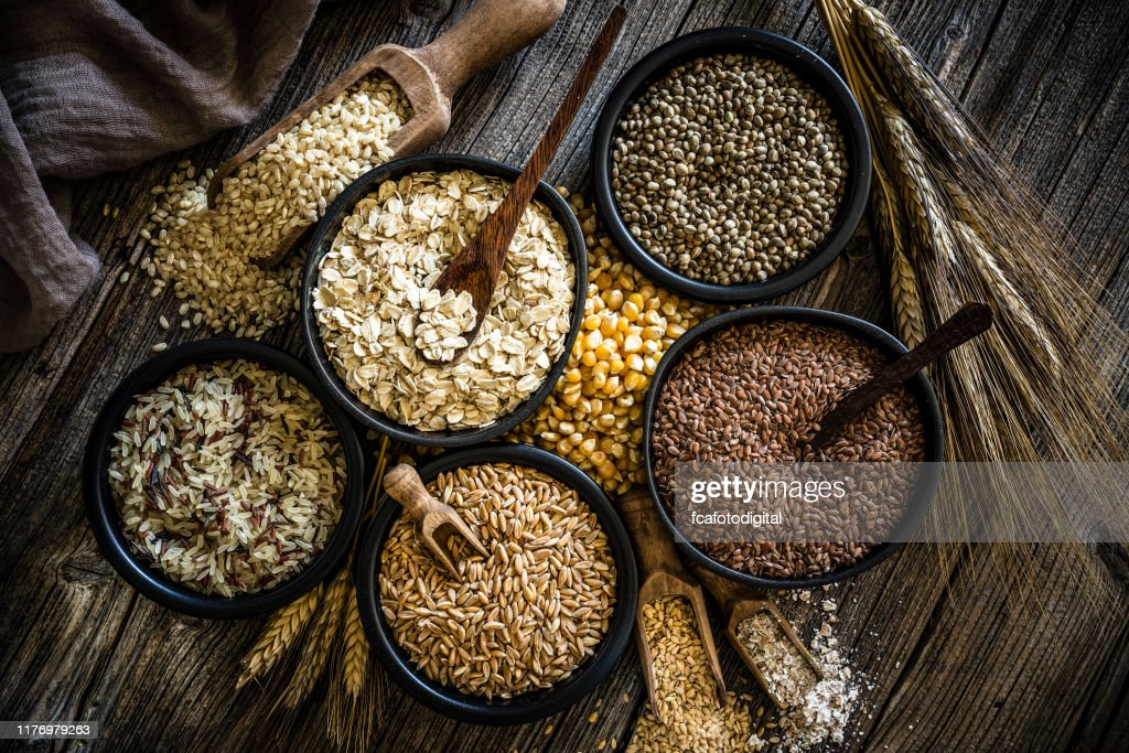 Large group of wholegrain food shot on rustic wooden table : Stock Photo