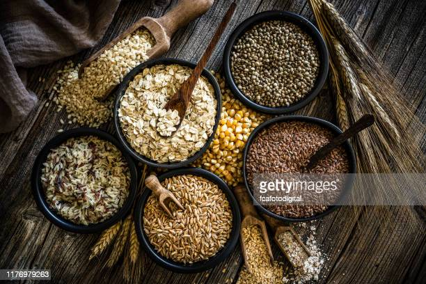 large group of wholegrain food shot on rustic wooden table - cereal plant stock pictures, royalty-free photos & images