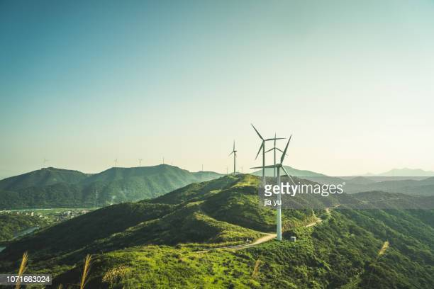 large group of wind turbines on the mountain near by sea - windmills stock photos and pictures