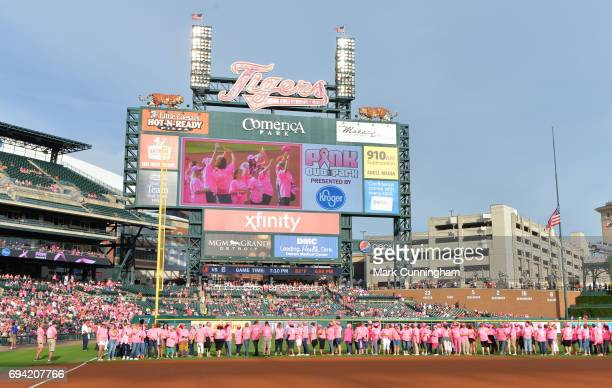 A large group of women dressed in pink stand together on the field for the Detroit Tigers Pink Out The Park promotion honoring breast cancer...