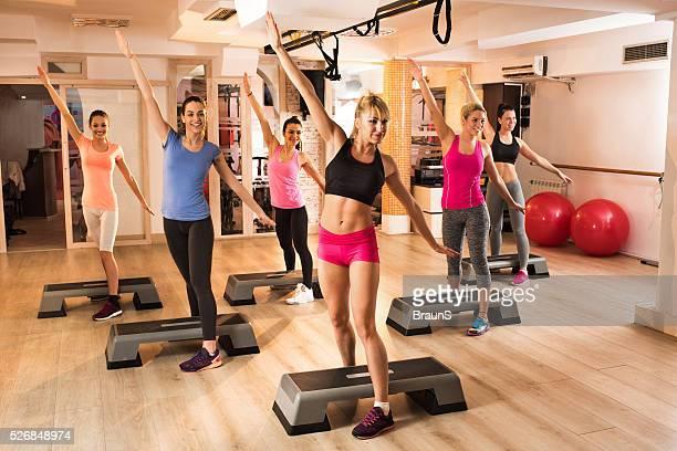 Grande grupo de mulheres na aula de aeróbica exercícios no ginásio.