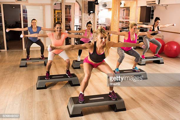Large group of women exercising step aerobics with dumbbells.
