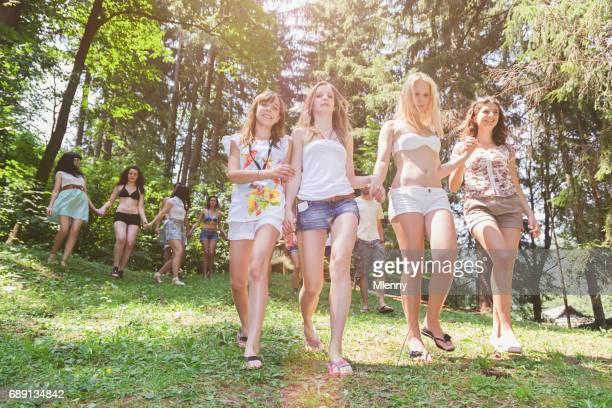 grand groupe de femmes marchant vers le bas de la colline vers le lac en été - mini short photos et images de collection