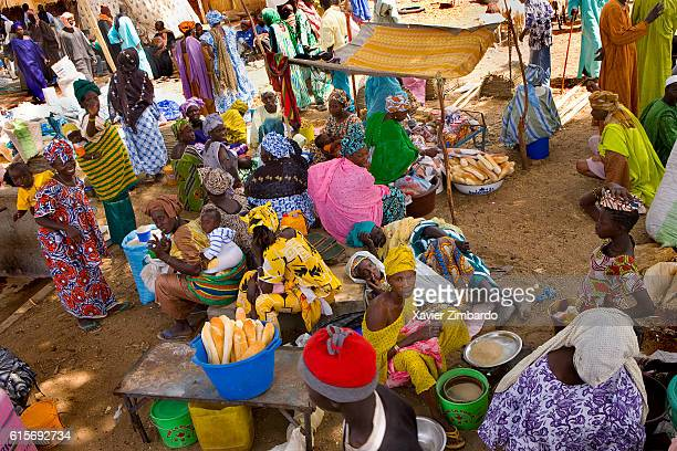 Large group of women wearing boubou and selling bread in a traditional village market on May 25 2007 at SaintLouis Senegal