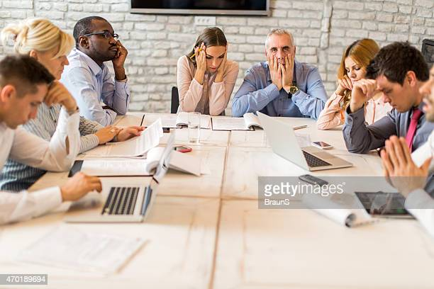 Large group of worried business people having a meeting.