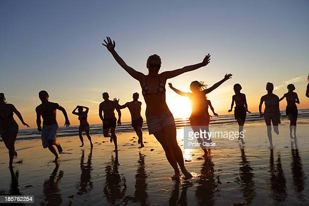 large group of young adults running on beach - crowd stock pictures, royalty-free photos & images