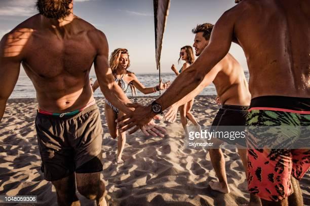 große gruppe von jugendlichen gruß einander nach volleyball am strand spielen. - strand volleyball stock-fotos und bilder