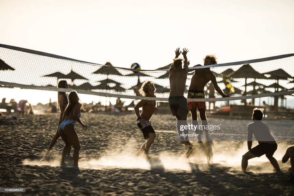Group Of Young People Playing Volleyball On Beach High-Res