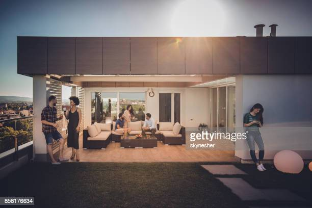 large group of young people relaxing during the day on penthouse balcony. - penthouse stock pictures, royalty-free photos & images