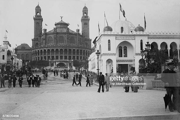 Large groups of well dressed people walking on the street during the Paris Exposition Universelle of 1900 by the Palis de l' Algerie and Palais du...
