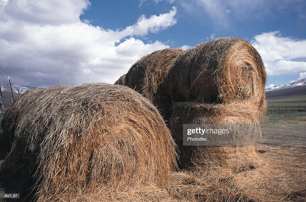 large hay bales stand stacked as mountains rise in the background under a blue sky with white clouds : Foto de stock