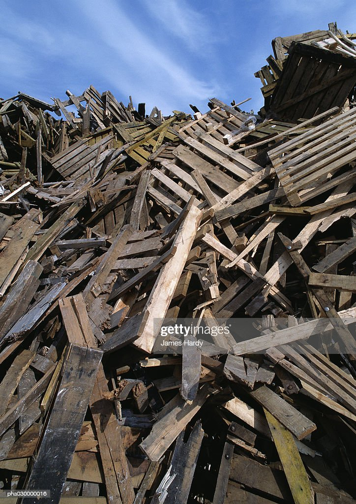 Large heap of wooden planks and pallets, blue sky in background. : Stockfoto