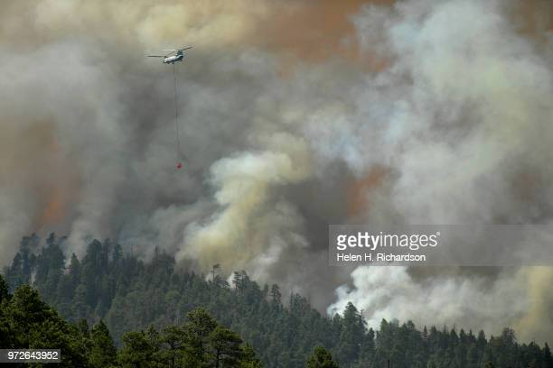 A large helicopter passes homes as it heads to make a water drop on the 416 fire on June 12 2018 in Hermosa Colorado The fire burning 23 miles...