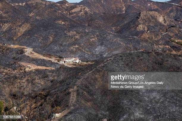A large home is surrounded by a charred landscape from the Woolsey fire in this view from Lobo Canyon road