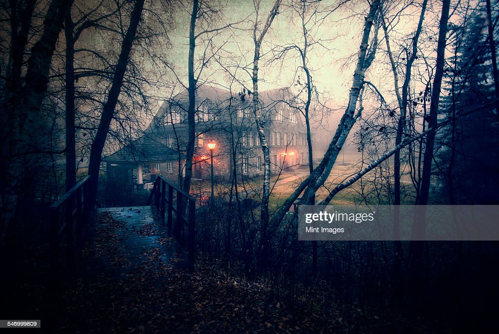 A large house at dusk with lights glowing. Woodland. A footbridge. : Stock Photo