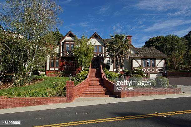 Large house with red brick stairs in the front entrance on a sloped road Saratoga California