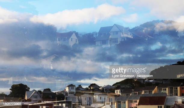 Large houses on Mt Cook, in central Wellington, are seen reflected in a window against sky and clouds. The latest housing affordability data from...