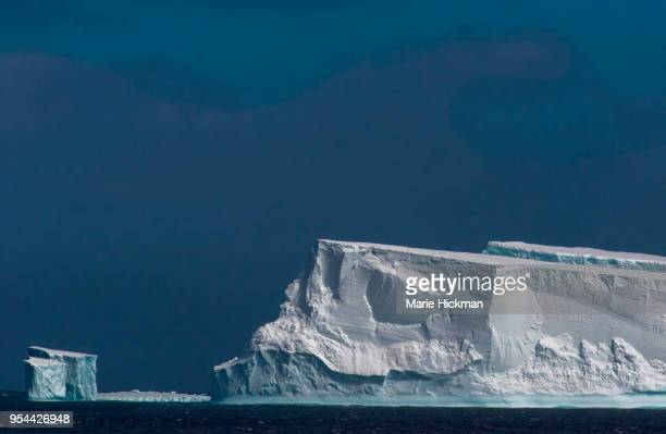 large iceberg and small iceberg behind it in antarctica. - images stock photos and pictures