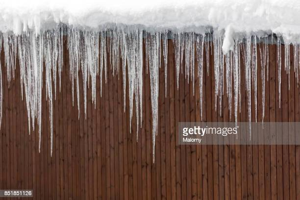 Large icicles hanging from the snow-capped roof of a log cabin - Koenigssee, Bavaria, Germany