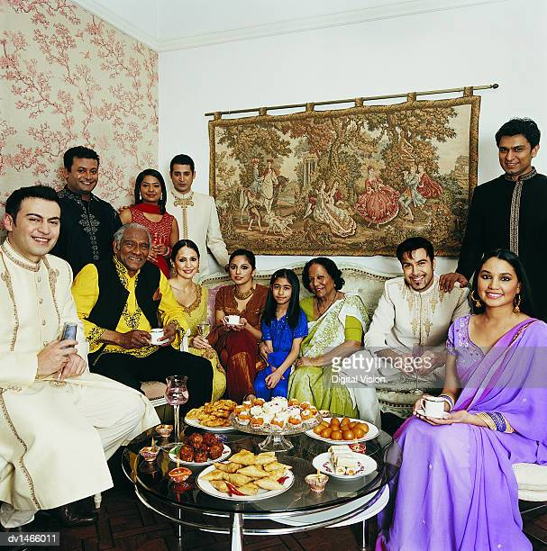 Large Indian Family Sit Round a Coffee Table